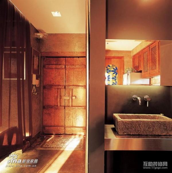 卫生间洗手盆外置,用一个石刻的水槽当洗手盆,与下面的不锈钢台面形成非常大的反差,入户门是在防盗门内侧安装的两扇古旧的街门,使整体装饰风格既有古典味道又有现代的拿来主义