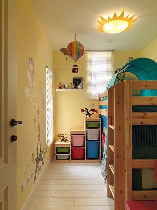 儿童房的墙面是淡黄色,很温馨,太阳吸顶灯,以及墙角的一些玩具收纳盒。