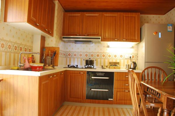 开放式厨房,原木色的橱柜、餐桌,以及地面砖,散发出自然清新的光泽。墙壁拼花砖,彰显出田园风。