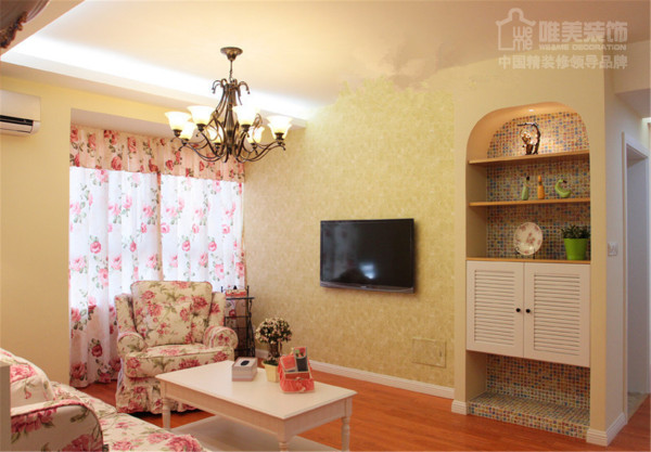 粉红色大花朵布艺沙发,搭配同样的布艺窗帘,浓郁的田园风立现,电视墙侧设立嵌入式储物柜,摆上精致小物件,底部白色漆百叶柜门,一切都是那么和谐美好!