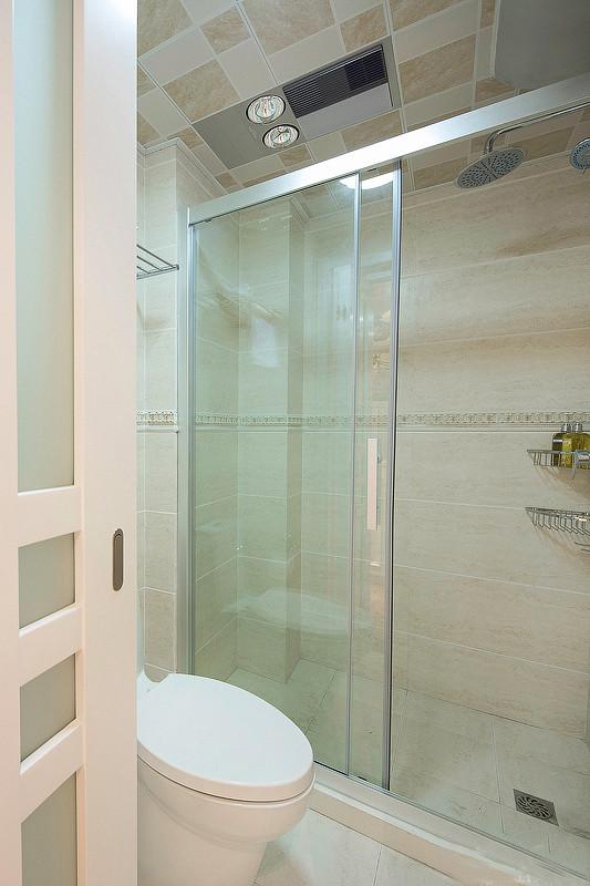 白色透明的浴室,采用了玻璃门的淋浴,没有浴缸,只有淋浴花洒。