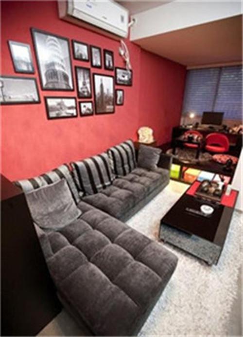正面,黑色银灰条纹抱枕,与上面的黑白照片相映成趣,左边有一个隐形开关。银灰绒布沙发,白色软毛地毯,整个大厅至高台以红黑为主,银白为辅。