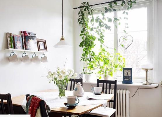 简单的餐座椅往往能带来最舒适的体验,深色的外表在一片白色中也比较显眼、醒目。窗台上放置的大盆绿植给餐厅带来不错的活力,小小的搁架也能放上不少的装饰。