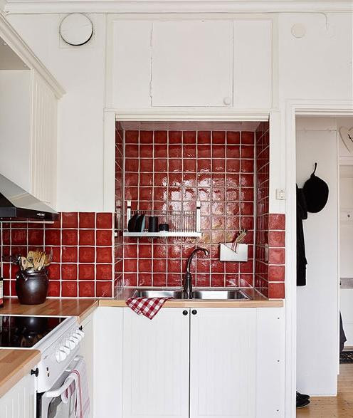 红色的墙面很抢眼。白色的空间总要用点其他色彩来调节、提升,那么为何不用红色呢。红色的瓷砖不仅容易打理而且特别的亮眼。木色的台面上方是红色,下方是白色,三者融洽的组合在一起。