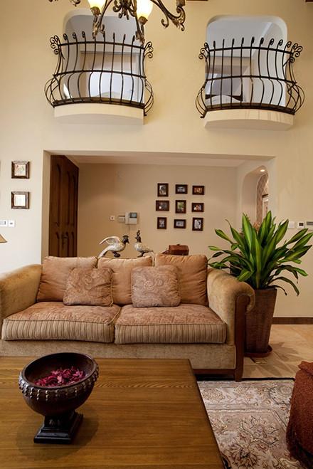 视觉的亮点来源于楼上的铁艺,也与上方的灯光相互呼应。是设计上的一个亮点。而沙发的颜色质地显得温暖,铺上华美的地毯,更加优雅,高贵。