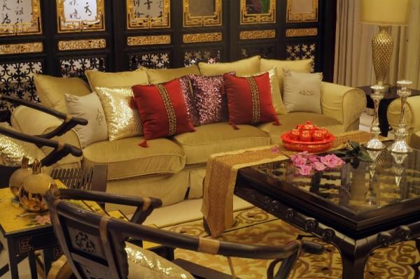 一组顶天立地的大型活动屏风成为客厅的主视点,精致的金漆木雕尽显古韵风情。一盏水晶吊灯用布艺围合。