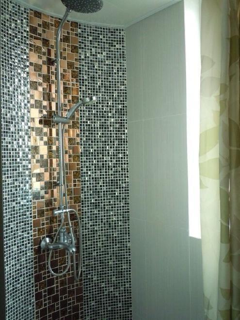 淋浴室的装修效果备显豪华,墙壁中间的大马赛克真有土豪金的样子。