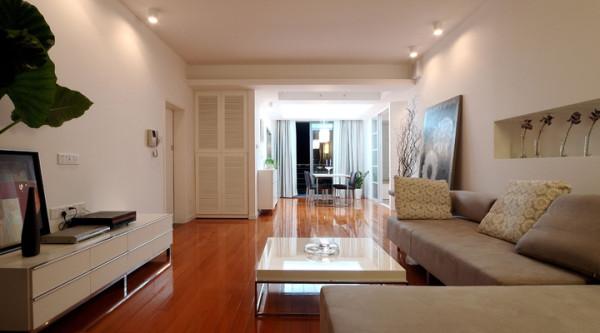 """客厅入户即见的""""软""""玄关,喷绘大幅装饰画,选画选重色,以夸张的图形比例来吸引眼球。现场制作的视听台结合构成高度有错,色调和谐的局部空间效果。"""