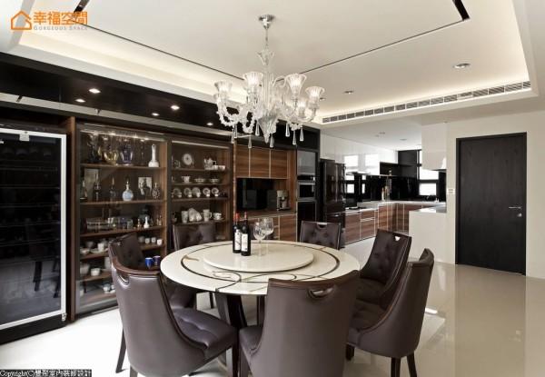 耀眼华美的水晶吊灯悬于界定餐厅场域的灰玻方块天花处,聚焦一进入招待熟客的餐厨与客房区的目光,兼具收纳与展示机能的柜体从餐厅一路延伸进入后方的厨房空间。