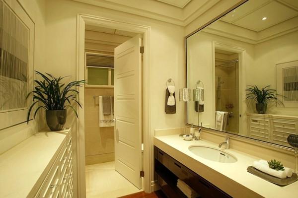 大面的落地玻璃隔离了浴室与外面的洗漱区,使整个卫浴间显得通透宽敞。洗漱台上的长镜方便主人洗漱时整理形象,镜子前方的小盆栽为空间增添了香气。整个卫浴间以地砖进行装修,体现一种大气和整齐。