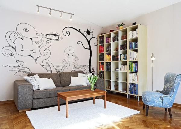 由于面积限制,客厅用的两人座灰色布艺小沙发,白色墙壁画上简线条抽象画作为装饰,旁边是格子书架,摆满了书,闲时也可以翻翻书、犯犯困。