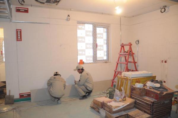 工人正在为业主,细心的去贴每一块护墙板。