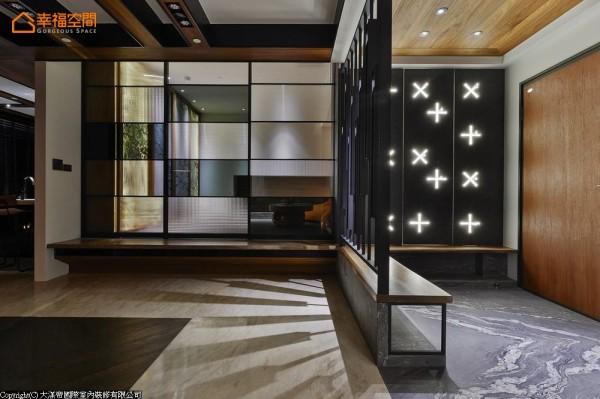 以烧面花岗石作为玄关落尘区的地材分野,结合LED照明效果,在一侧的十字语汇中,暗藏吊帽勾挂的基能巧思。