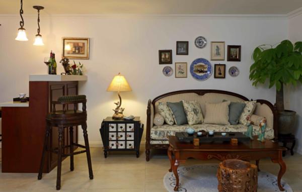 沙发背后的装饰墙。瓷盘以及装饰画,细看之下有些小画里裱的是植物标本,有些是精致的小油画。大青花瓷盘中间是人物图片。做旧的色彩和画品斑驳的边框,似在娓娓道来一段段远渡重洋的故事。