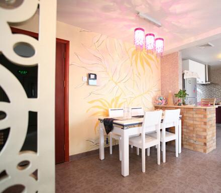 客厅一角,即被做成餐厅,墙面延伸了客厅背景墙的藤蔓花纹;略带欧式风格装饰的四方桌为餐桌,用红砖砌成的隔断墙面将空间完美的分割开来。