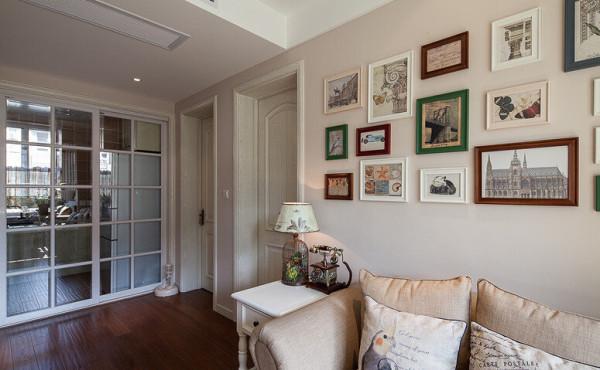 沙发背后的照片墙布满了装饰画。柜子上的鸟笼台灯很有特色,还放了一架复古电话机做装饰。