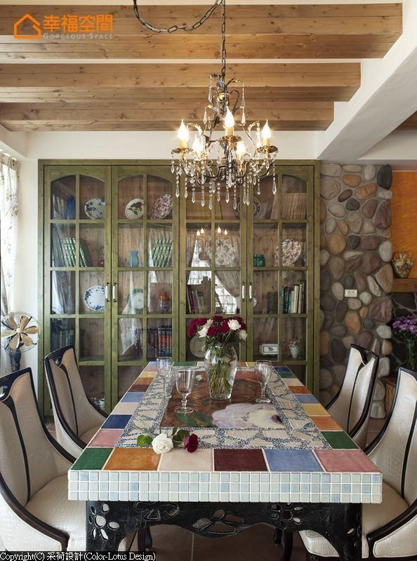 与客厅色彩区隔的墨绿原木手染餐柜,将屋主的收藏整齐的展示在古典格栅中,成为用餐时值得一同品味的空间主景,搭上一盏水晶吊灯,晕开了用餐时的浪漫氛围。