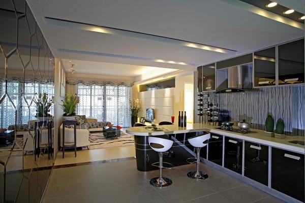 厨房和客厅采用开放式结构,还设置有吧台,蛋椅和吧台形成完美的结合,柜体采用黑色,厨房墙壁用灰镜饰面,这样感觉就比较空阔不压抑 。