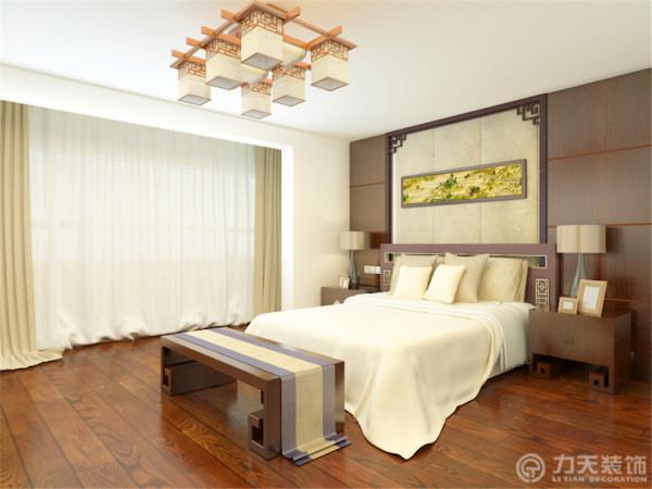 卧室顶面没有做过多的装饰,只是一个平顶,吊有中式吊灯,床头背景墙中间采用软包,两边是拉缝木板,与客厅相对应,整个空间都采用木地板。整体的家具摆设彰显出浓厚的新中式氛围。