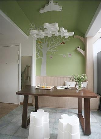 绿色的背景墙延伸到吊顶,原木卡座和延伸的树枝造型、餐桌,白云造型的吊灯,小餐厅仿佛在大自然中。