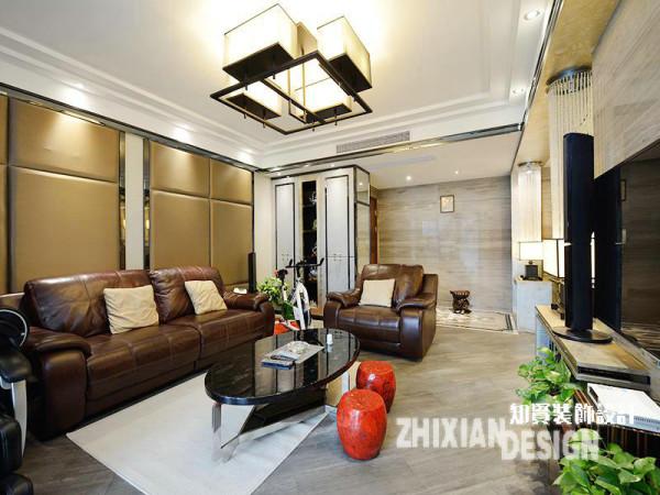 """客厅的现代感强烈,各式几何图案的运用随处可见。软包处理的背景墙和皮质的沙发组合成风景一致的""""软性""""存在,中和了墙壁设计的硬度和镜面感。"""