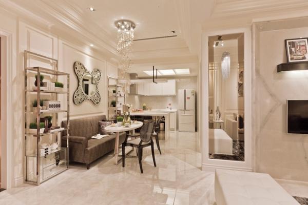 客厅的设计简约大气、线条洗练,淡色系墙面、天花板、沙发与深色系的茶几、沙发后背墙纸相得益彰,赋予空间平衡之美 。