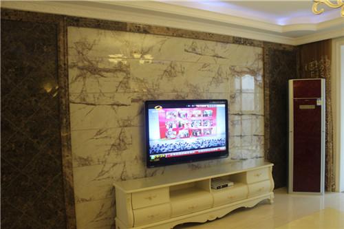 沙发背景简单的艺术墙纸,与电视背景相呼应对比之。阳光从推门外透过幔纱映在暖米色地砖上