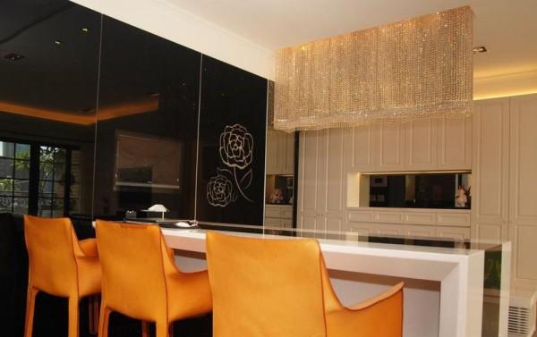 在黑色烤漆门片上大器绽放,不间断的黑巧藏住酒杯展示,也延续起电视墙面与柱体包覆