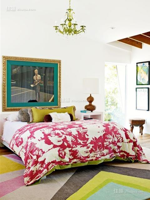 主卧中,鲜艳大胆的印花床品、色块丰富的地毯、大幅装饰画显示出卧室不拘一格的个性