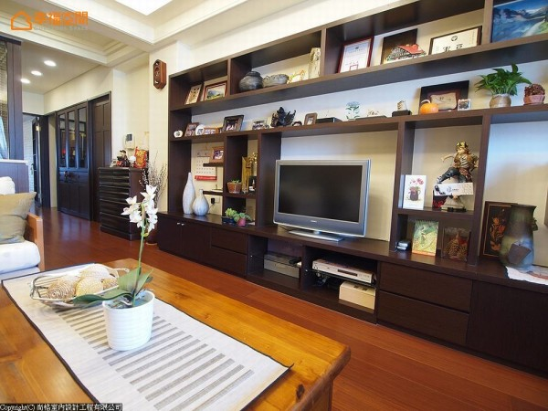 舍弃常见的大理石电视墙,选择运用订制木柜,展示丰富的生活物品,让空间充满屋主回忆。