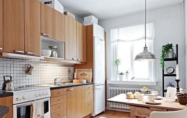 橱柜选用实木材质,清晰的木质肌理和自然的色彩打造出一个森系的世界。厨房在收纳设计上也下了功夫,订制的橱柜很好地开辟出冰箱的位置,吊柜上留有一定位置,可将不常用的物品高高搁置。