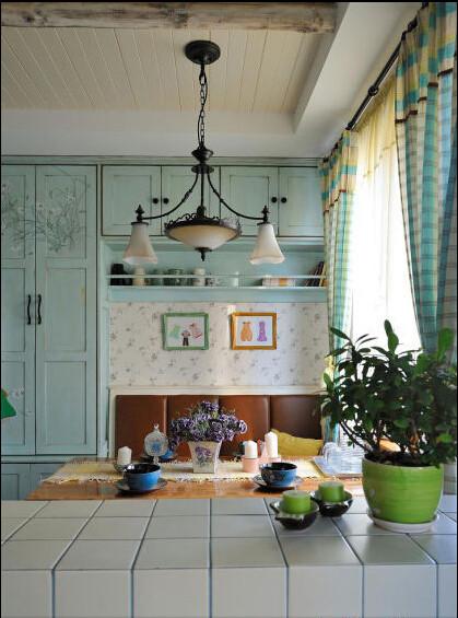 从厨房看餐厅的角度,餐厅的正面墙都做成了淡蓝色的储物柜,靠近餐桌的位置做了一小截沙发。
