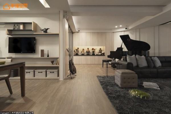 沙发与格局斜面形成的空间摆置三角钢琴,连续的木质柜体可收纳琴谱,此外也放置男主人收藏的乐器,与爵士乐公仔。