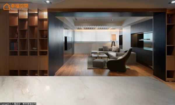 利用柜体厚度与天花降板跳接深色木皮,延伸至沙发背墙与电视主墙,创造框景的深邃效果。