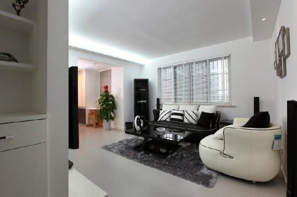 窗户加上百叶帘,透过帘子可看到室外风景,视觉空间扩展开来,让黑白冷色调的客厅多了些柔和情致