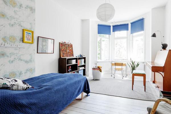 明亮的飘窗挂上蓝色的窗帘,和单人床一致的天蓝色,营造出静谧的氛围。淡色的地图墙纸打破了墙面的单调感,多了几分趣味。