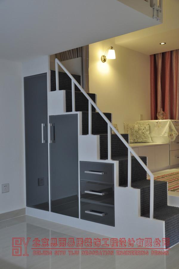 互应空间色彩主题,以黑白为主色调,用红色来点缀空间品位。所以我们把这里的楼梯柜门全部设计成了灰镜。达到扩展空间的效果,同时又互应了整体空间色调。