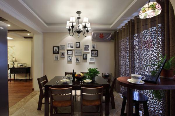 餐厅的餐桌选择实木为主,深红色的实木餐桌搭配纹样丰富的餐具相得益彰,餐厅墙面的照片墙将来会是整个家旅游归来的分享区。