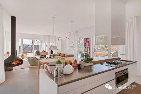 客厅背后便是开放式厨房,不锈钢台面充满现代气息。