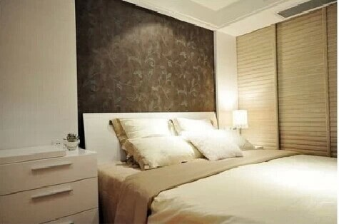 卧室中的睡床背景采用壁纸,降低了卧室的亮度