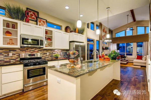 厨房的空间仿佛是一个色彩派对,通透的窗户映照出暮色来临之前的蓝天,白色橱柜清新利落,散落在这之间的是跳跃的橙色、红色、黄色装饰,美观时尚。