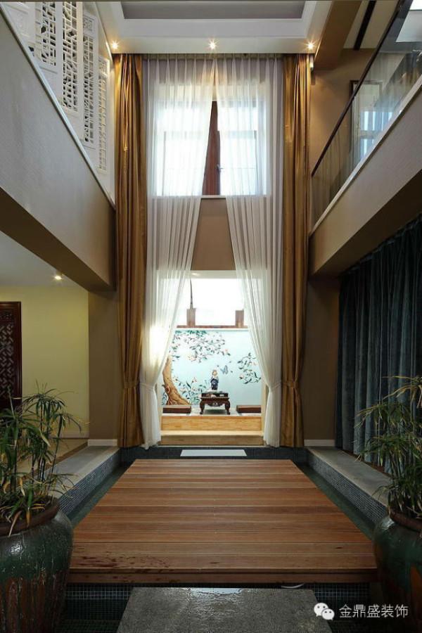 超高挑空玄关,简洁的空间线条,木质地板的尽头是水墨画的屏风,颇有中国写意画的飘逸风情。而白色的轻纱,装点出空间的梦幻与浪漫感。