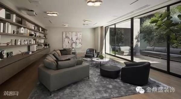 这间起居室位于别墅的后面,与露台相连,也通过一面大型落地玻璃窗让其成为阳光房。整面墙设计成了书柜,让这间起居室兼具了书房的功能。