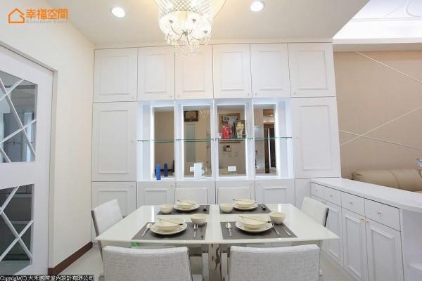 华丽的水晶灯下,古典的口字框线板、镜面与玻璃层架,于餐厅段落搭构对称的收纳景致。