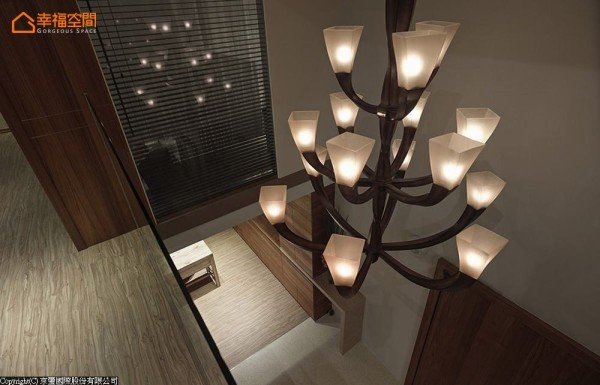 挑空区的立体造型灯饰,透过清玻成为2F梯间的端景,两侧分别为卧房及目前作为更衣间的客房。