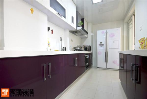 """这套厨房的装置可以说相当的时尚前卫,""""二""""字型的厨柜充实了厨房的空间 厨柜的台面和吊柜同样采取了白色的基调。不过暗红色烤漆的门板陡然打破了这份沉静。白底紫花的双开门冰箱则在两者中起到了过度作用。"""
