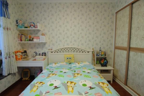 """儿童房,米白碎纹壁纸让温馨铺满全房,象牙白小小床铺旁,是同样精巧可爱的书柜书桌。各类玩偶随性摆放,风格不一,颜色多变,以这般""""不定性""""的装饰,守护着孩子们无拘无束,不染世俗教条的纯真。"""