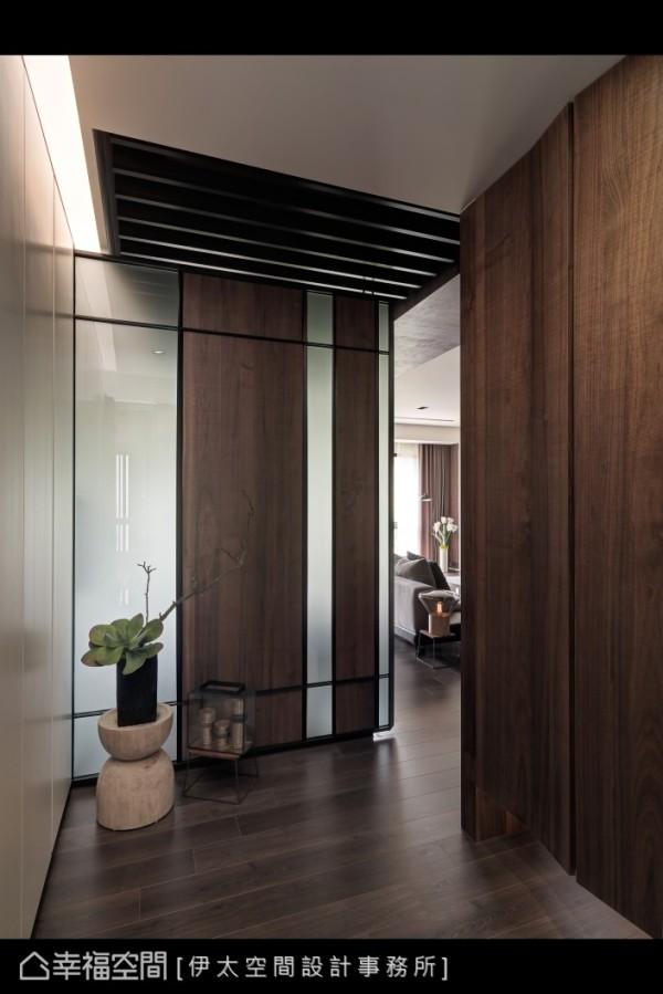 墨色的铁件框定,雾面玻璃与木质材料虚实相生的构图为玄关景致。
