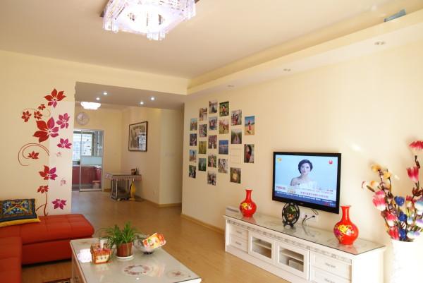 暖意盎然的客厅也反映了主人对生活充沛的热爱。电视背景墙并未做过多建筑处理,乳白色原墙左侧,DIY照片墙盛满了回忆与欢笑,实木电视柜右边,细腰白瓷瓶里花团锦簇。