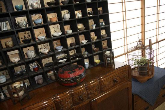 刻有花纹的的木质抽屉,显得古典优雅,下方的收纳柜,具有大容量的收纳功能,非常实用。网格式的收纳柜,摆放着各式各样的瓷碗,精美别致。